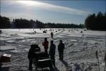 Massa folk på isen väl framme vid sjön.